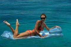 Femme dans le bikini rouge détendant sur le dispositif de flottement Photo libre de droits