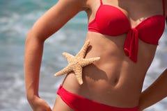 Femme dans le bikini rouge sur la plage avec des étoiles de mer photo libre de droits