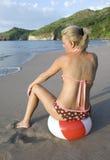 Femme dans le bikini se reposant sur la bille de plage sur la plage Photographie stock