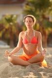 Femme dans le bikini se reposant sur la plage dans la pose de lotus photos libres de droits