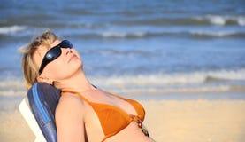 Femme dans le bikini se trouvant sur le sourire de plage Photographie stock libre de droits