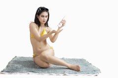 Femme dans le bikini utilisant le sunblock Photographie stock