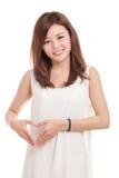 Femme dans le blanc avec des mains dans la forme d'un coeur Image stock
