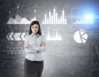 Femme dans le bleu et six graphiques sur le tableau noir Images stock