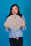 Femme dans le bleu et une horloge Image stock