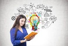 Femme dans le bleu lisant un livre, une idée et un plan photographie stock libre de droits