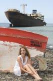 Femme dans le bord de la mer près d'un bateau abandonné Photo stock