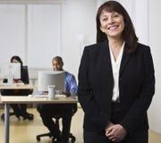 Femme dans le bureau avec des collègues Photo stock