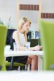 Femme dans le bureau regardant le smartphone Image stock