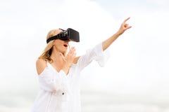 Femme dans le casque de réalité virtuelle dirigeant le doigt Images libres de droits