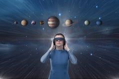 Femme dans le casque de VR recherchant aux planètes 3D contre le ciel bleu avec la fusée Image stock