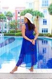 Femme dans le chapeau blanc du soleil détendant dans la piscine dans la pleine robe bleue Photographie stock libre de droits