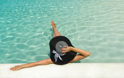 Femme dans le chapeau détendant à la piscine Photo stock