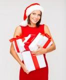 Femme dans le chapeau d'aide de Santa avec beaucoup de boîte-cadeau Photos libres de droits