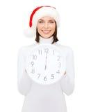 Femme dans le chapeau d'aide de Santa avec l'horloge montrant 12 Image libre de droits