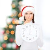 Femme dans le chapeau d'aide de Santa avec l'horloge montrant 12 Photographie stock