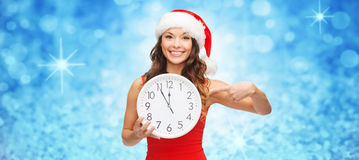 Femme dans le chapeau d'aide de Santa avec l'horloge montrant 12 Photos libres de droits