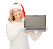 Femme dans le chapeau d'aide de Santa avec l'ordinateur portable Image stock