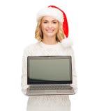 Femme dans le chapeau d'aide de Santa avec l'ordinateur portable Photos stock