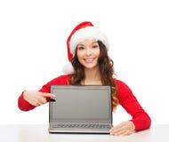 Femme dans le chapeau d'aide de Santa avec l'ordinateur portable Photo stock