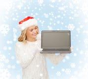 Femme dans le chapeau d'aide de Santa avec l'ordinateur portable Photographie stock