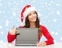 Femme dans le chapeau d'aide de Santa avec l'ordinateur portable Photo libre de droits
