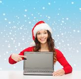 Femme dans le chapeau d'aide de Santa avec l'ordinateur portable Photos libres de droits