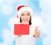Femme dans le chapeau d'aide de Santa avec la carte rouge vierge Images stock