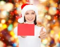 Femme dans le chapeau d'aide de Santa avec la carte rouge vierge Photos stock