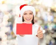 Femme dans le chapeau d'aide de Santa avec la carte rouge vierge Image stock