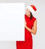 Femme dans le chapeau d'aide de Santa avec le conseil blanc vide Photographie stock libre de droits