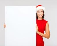 Femme dans le chapeau d'aide de Santa avec le conseil blanc vide Photos libres de droits