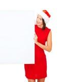 Femme dans le chapeau d'aide de Santa avec le conseil blanc vide Images stock