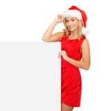 Femme dans le chapeau d'aide de Santa avec le conseil blanc vide Photos stock