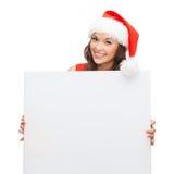 Femme dans le chapeau d'aide de Santa avec le conseil blanc vide Photographie stock
