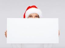 Femme dans le chapeau d'aide de Santa avec le conseil blanc vide Photo stock
