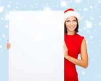 Femme dans le chapeau d'aide de Santa avec le conseil blanc vide Image libre de droits