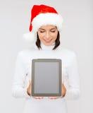 Femme dans le chapeau d'aide de Santa avec le PC de comprimé Image stock