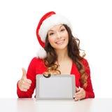 Femme dans le chapeau d'aide de Santa avec le PC de comprimé Photo libre de droits