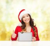 Femme dans le chapeau d'aide de Santa avec le PC de comprimé Photographie stock