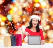 Femme dans le chapeau d'aide de Santa avec le PC de comprimé Photos stock