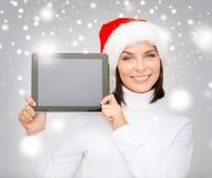 Femme dans le chapeau d'aide de Santa avec le PC de comprimé Image libre de droits