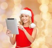 Femme dans le chapeau d'aide de Santa avec le PC de comprimé Photos libres de droits