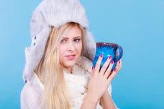 Femme dans le chapeau d'hiver buvant de la tasse Images stock