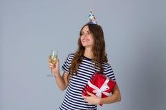 Femme dans le chapeau de célébration tenant un présent et un verre Photo stock