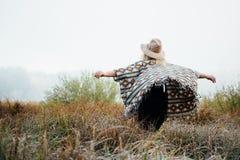 Femme dans le chapeau de feutre à large bord et position authentique de poncho dans la haute herbe brune au matin brumeux photos libres de droits