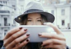 Femme dans le chapeau de feutre gris, promenade enjoing de ville, extérieure Image libre de droits