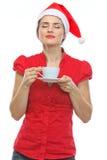Femme dans le chapeau de Noël appréciant la cuvette de café Photos stock