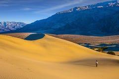 Femme dans le chapeau de paille photographiant des vagues de sable Photo libre de droits