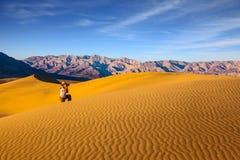 Femme dans le chapeau de paille photographiant des vagues de sable Images libres de droits